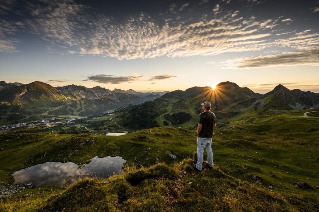 Sonnenuntergang mit Blick auf Obertauern, Mit See und Person im Vordergrund